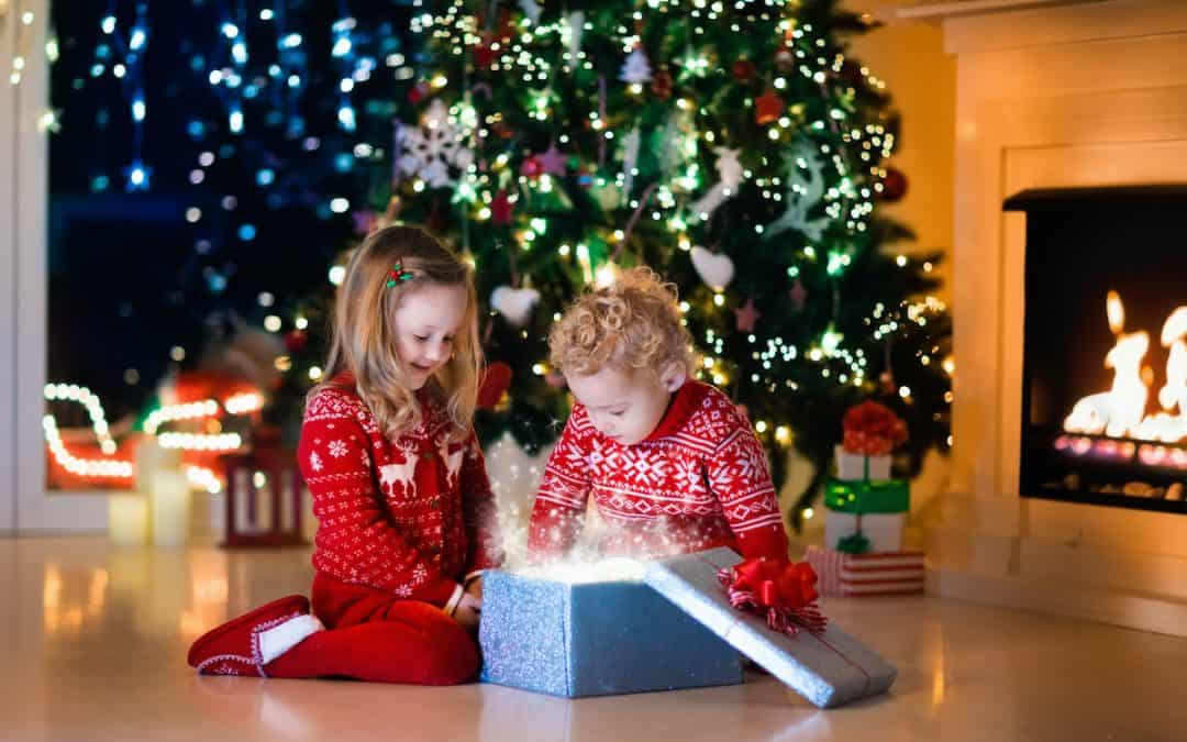 Toddlers opening up Christmas gifts. The perfect holiday gift guide for toddlers.
